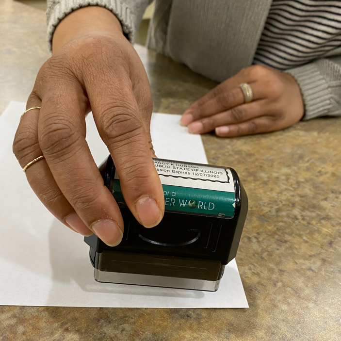 A person using a notary stamp